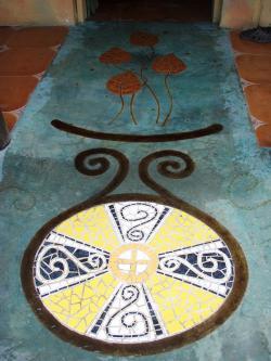 Entrada de restaurante con suelo de cemento pulido con incrustación de motivo en mosaico
