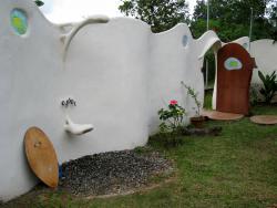 Muro exterior de arquitura organica con ducha de diseño y decorado con cristales artesanales.