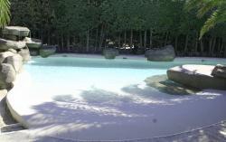 Piscina tropical tipo playa con entrada en  rampa